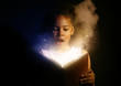 canvas print picture - Surprised African-American girl reading magic book on dark background