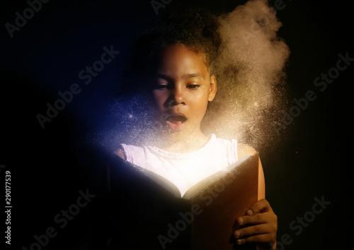 Obraz Surprised African-American girl reading magic book on dark background - fototapety do salonu
