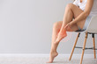 canvas print picture - Woman suffering from pain in leg while sitting on chair near light wall