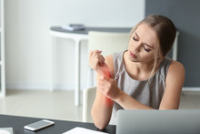 Young Woman Suffering From Pain In Wrist At Workplace