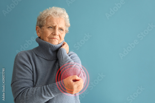 Fotografía  Senior woman suffering from pain in elbow on color background