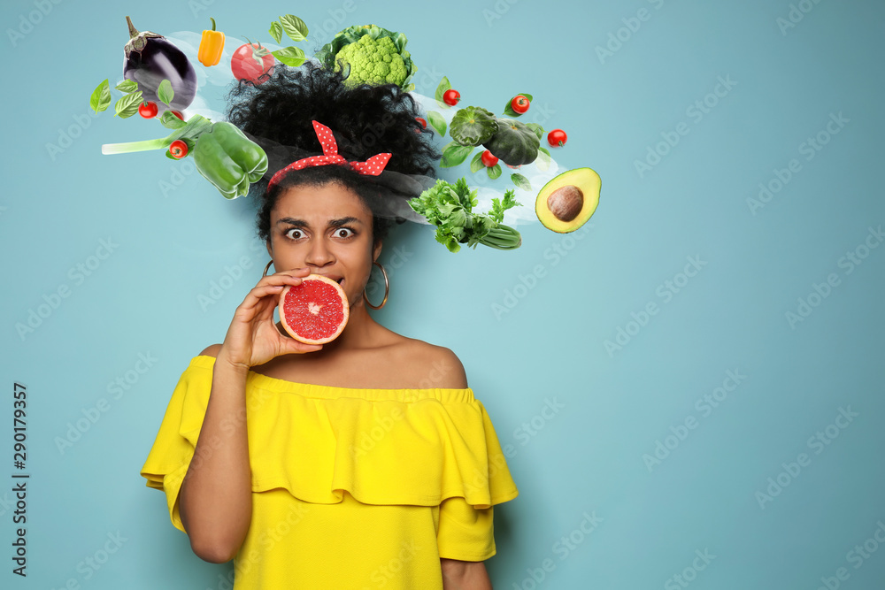 Fototapeta Portrait of young African-American woman with grapefruit on color background