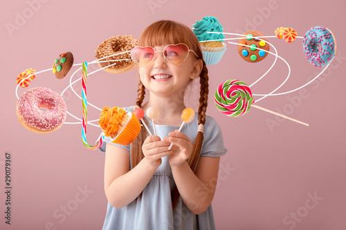 Photo Cute little girl with lollipops on color background