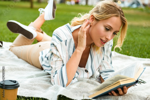 Poster Attraction parc Beautiful young blonde girl relaxing on a lawn at the park