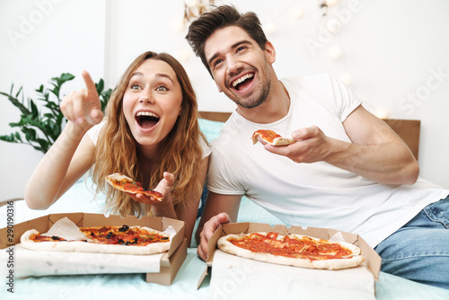 Fototapeta Image of cheerful happy couple lying on bed at home and eating pizza obraz