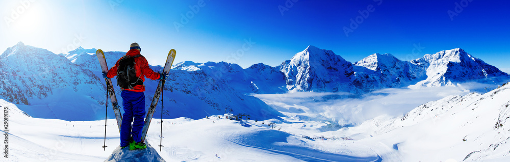 Fototapety, obrazy: Mountaineer backcountry ski resting along a snowy ridge with skis in the backpack. In background blue sky and shiny sun and Ortler in South Tirol, Italy.  Adventure winter extreme sport.