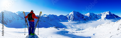 Canvas Prints Dark blue Mountaineer backcountry ski resting along a snowy ridge with skis in the backpack. In background blue sky and shiny sun and Ortler in South Tirol, Italy. Adventure winter extreme sport.