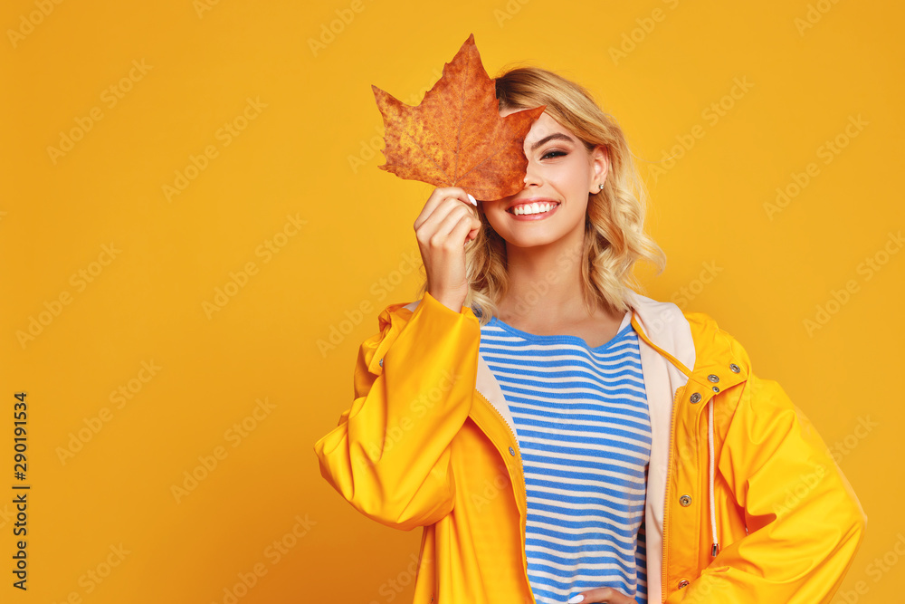 Fototapeta happy emotional girl with autumn leaves on colored yellow background.