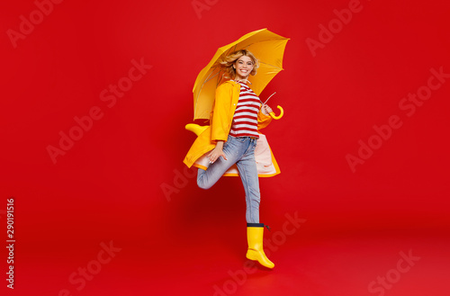 fototapeta na drzwi i meble young happy emotional cheerful girl laughing with yellow umbrella on colored red background.