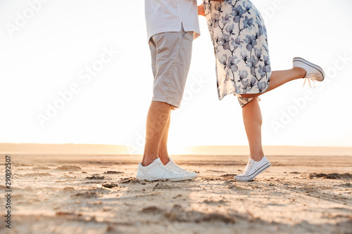 Cropped photo of beautiful caucasian couple kissing and hugging while walking on Canvas Print