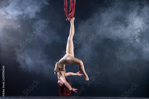 Kobieta atletyczna, seksowna i elastyczna powietrzna artystka cyrkowa z rudą tańczącą w powietrzu na jedwabiu