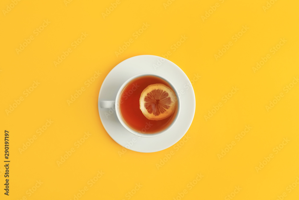 Fototapeta Cup of tea on yellow background, top view