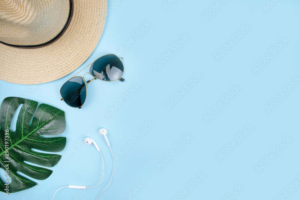 Fototapeta Top view of travel accessories with sun glasses, hat, and leaves on a blue background. - obraz na płótnie