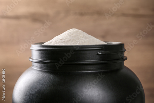 Black jar full of protein powder on brown background, closeup