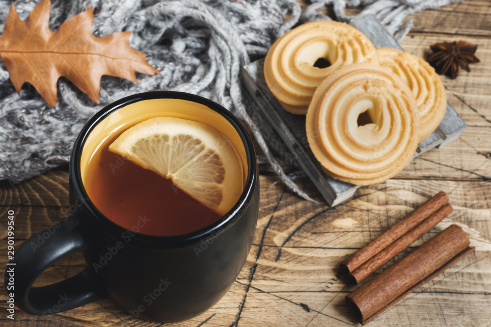Fototapeta Autumn still life with cup of tea, cookies, sweater and leaves on wooden background. concept of cozy autumn, fall season