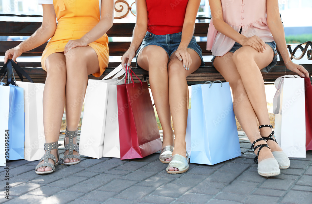 Fototapety, obrazy: Young women with shopping bags sitting on bench in park