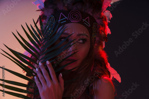 Portrait of sexual woman in headdress of feathers standing behind plant leave and looking aside