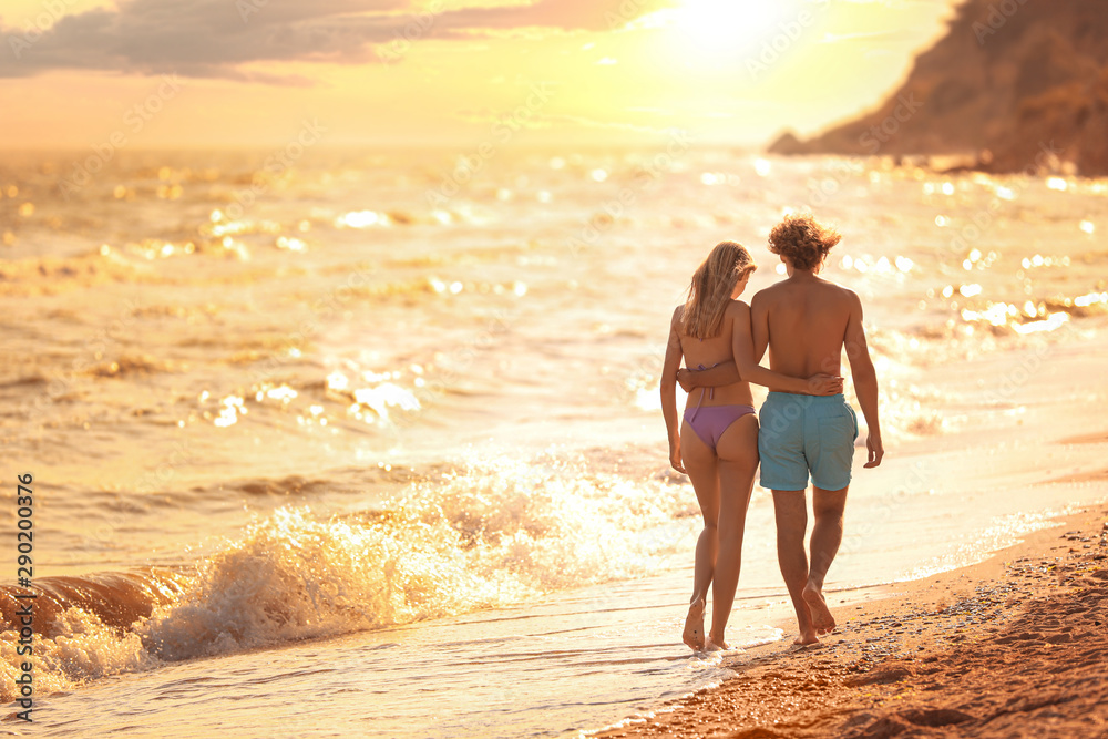 Fototapety, obrazy: Young woman in bikini and her boyfriend walking on beach at sunset. Lovely couple