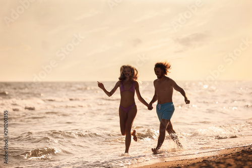 Carta da parati  Young woman in bikini and her boyfriend having fun on beach at sunset