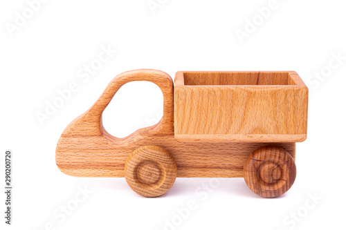 Photo of a wooden car  of beech. Toy made of wood retro truck on a white isolated background. A toy for entertaining children and resting parents