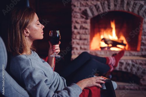 Obraz Cozy home. Close up of young woman drinking red wine near the fireplace. - fototapety do salonu