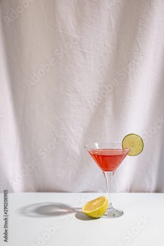 Fotografía  Half lime with cocktail drink garnish with cocktail on desk against isolated on