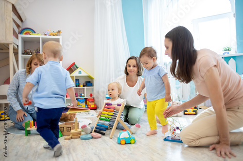 Small babies with their parents play in nursery