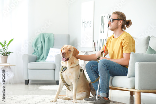 Tablou Canvas Blind young man with guide dog at home