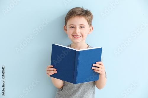 Obraz Little boy reading book on color background - fototapety do salonu