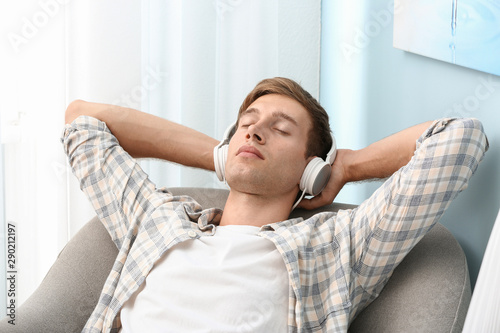 Poster Ecole de Danse Handsome young man relaxing and listening to music at home