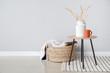 Leinwanddruck Bild Table and wicker basket with plaid near light wall
