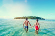 Honey moon on the sea shore. Back view of loving couple bathing together on beautiful tropical island beach.