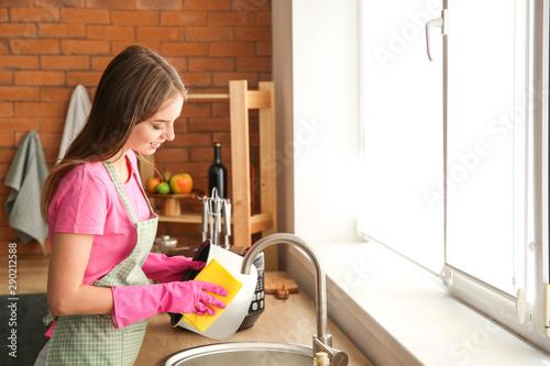 Fotomural  Woman washing modern multi cooker in kitchen