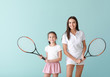 Leinwandbild Motiv Little girl and her mother with tennis rackets on color background
