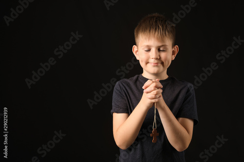 Praying little boy on dark background Canvas Print