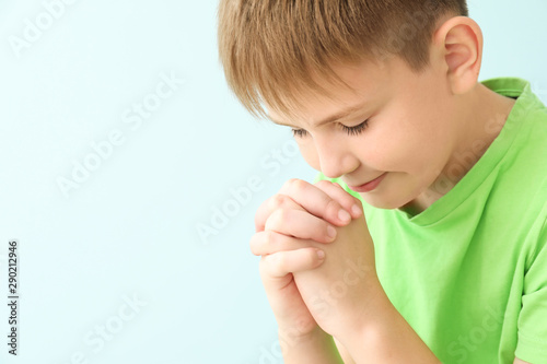 Photo Praying little boy on color background