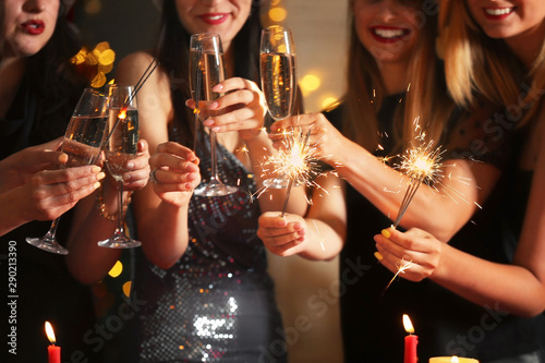 Poster de jardin Bar Happy women with Christmas sparklers and glasses of champagne at party