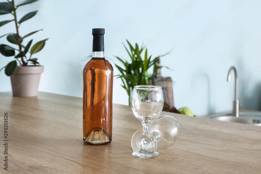 Fototapeta Bottle of alcoholic drink and empty glasses on kitchen table