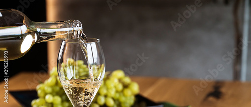 Poster de jardin Bar Pouring White wine with branches of grapes on a wooden table.