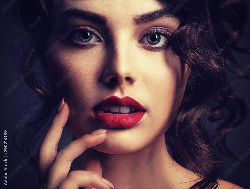 Fototapeta Face of a beautiful woman with a smoky eye makeup and red lipstick