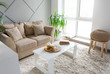 Leinwanddruck Bild Cozy sofa with table and tropical plant in stylish interior of room