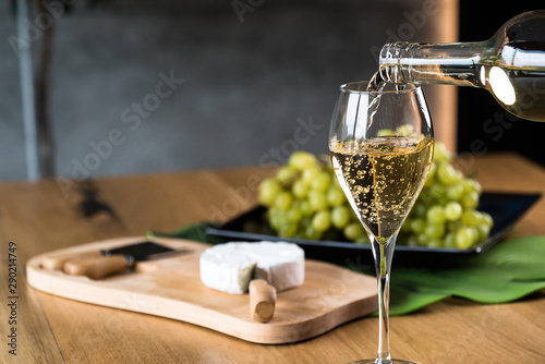 Foto op Canvas Alcohol Pouring White wine with branches of grapes on a wooden table.