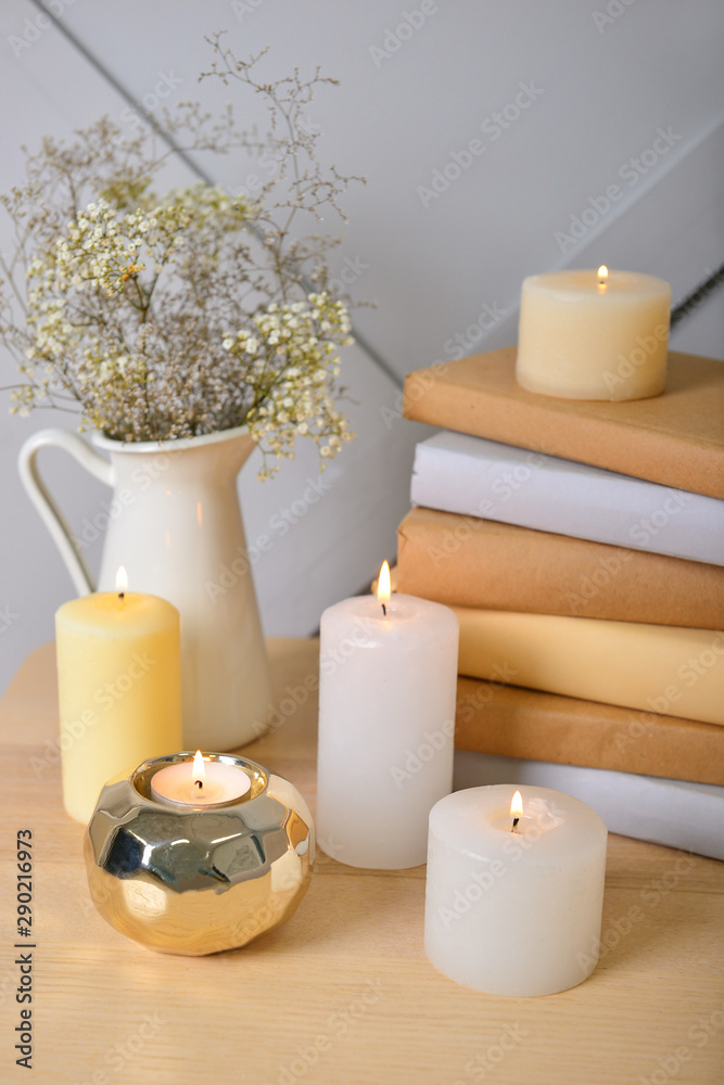 Fototapety, obrazy: Beautiful burning candles with books on table in room