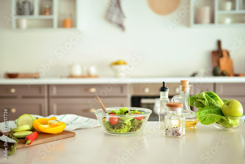 Bowl with salad and ingredients on kitchen table Tableau sur Toile