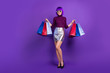 canvas print picture - Full length photo of stylish lady holding packs in hands wear trendy outfit isolated purple background