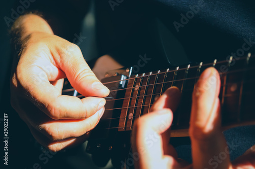 Playing the guitar. Guitarist's hand dynamic motion. Musical lifestyle background. Macro closeup. - 290222117