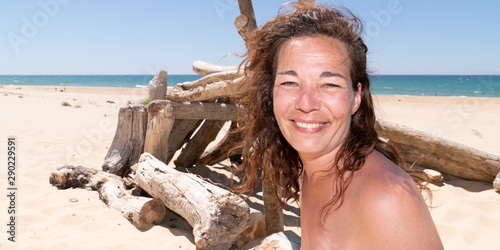 Fototapeta  Brunette forties woman in low top on the beach on a sunny day happy smile in web