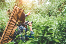 Couple Of Asian People Holding Binoculars Telescope In Forest Looking Forward To Destination. People Lifestyles And Leisure Activity. Nature And Backpacker Traveling Jungle Background. Bird Watching