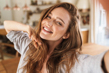 Beautiful happy ginger woman indoors at home take selfie by camera.