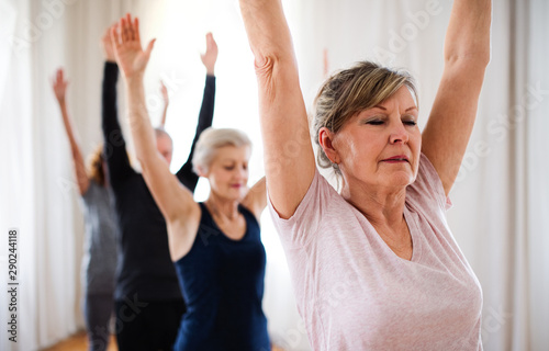 Fotografia  Group of senior people doing yoga exercise in community center club